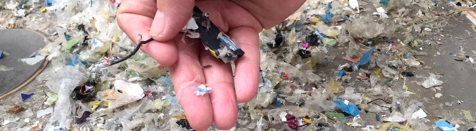 Eine Hand hält Plastikteile in die Kamera