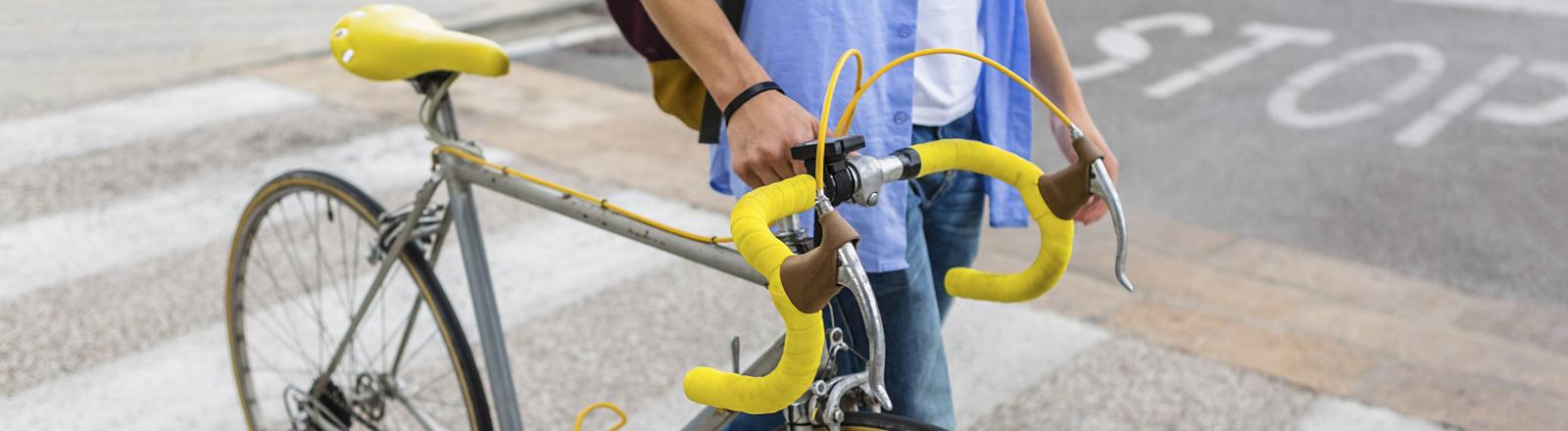Ein Mann schiebt sein Rennrad über einen Zebrastreifen.