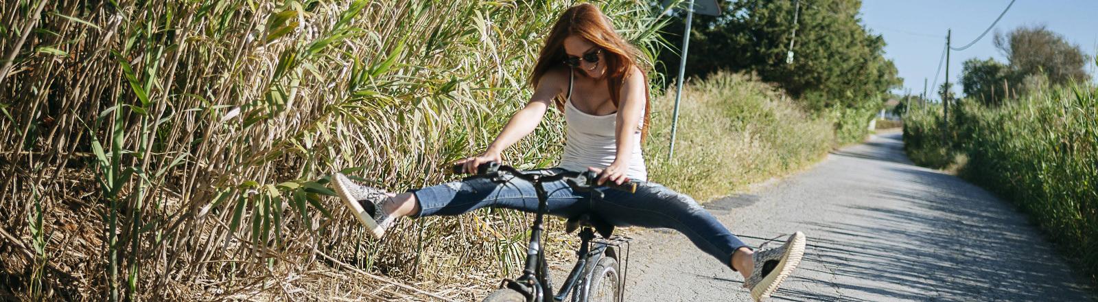 Eine junge Frau sitzt auf einem Fahrrad und streckt die Beine zu den Seiten in die Luft.