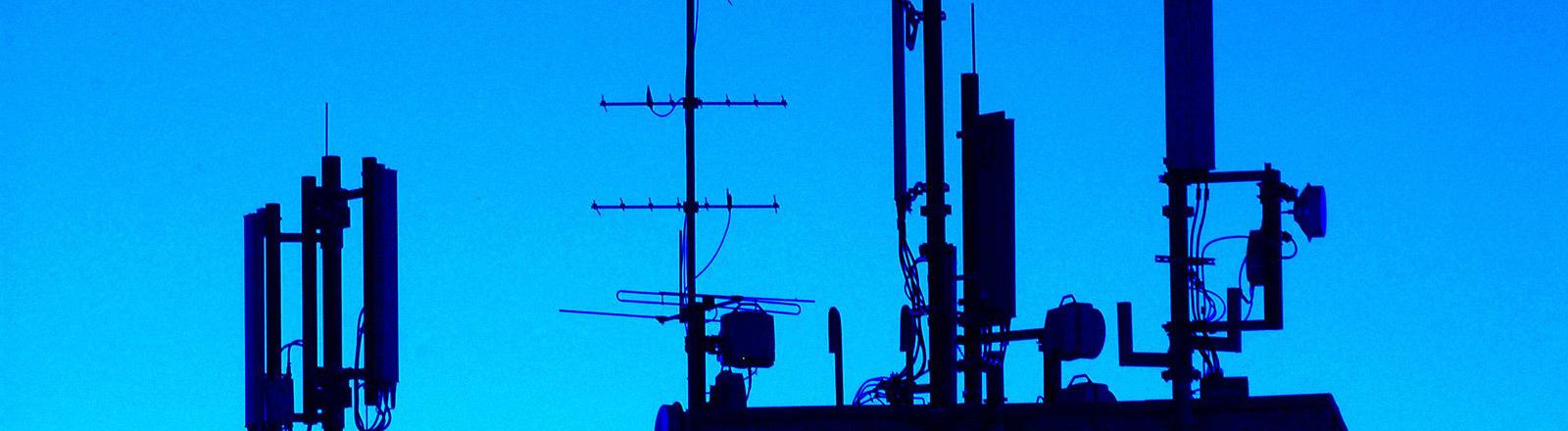 Funkmasten auf einem Gebäudedach.