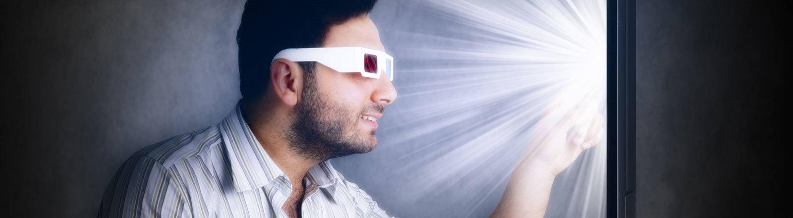 Mann mit 3D-Brille berührt Bildschirm
