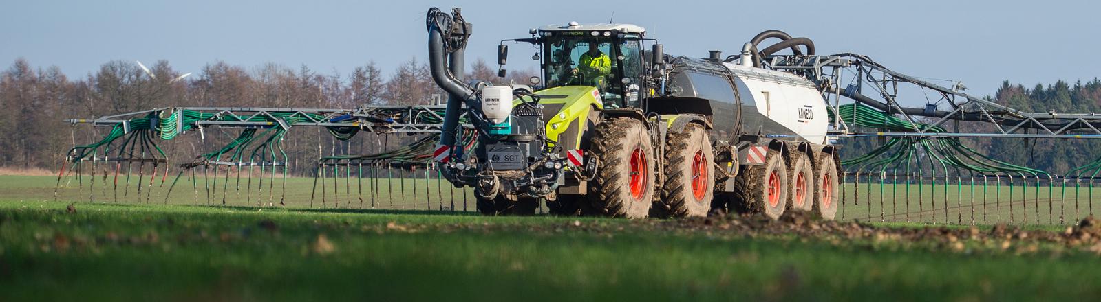 Ein Landwirt bringt mit seinem Gespann, Gülle auf einem Feld aus.