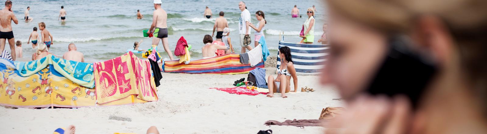 Eine Frau telefoniert im Urlaub am Strand.