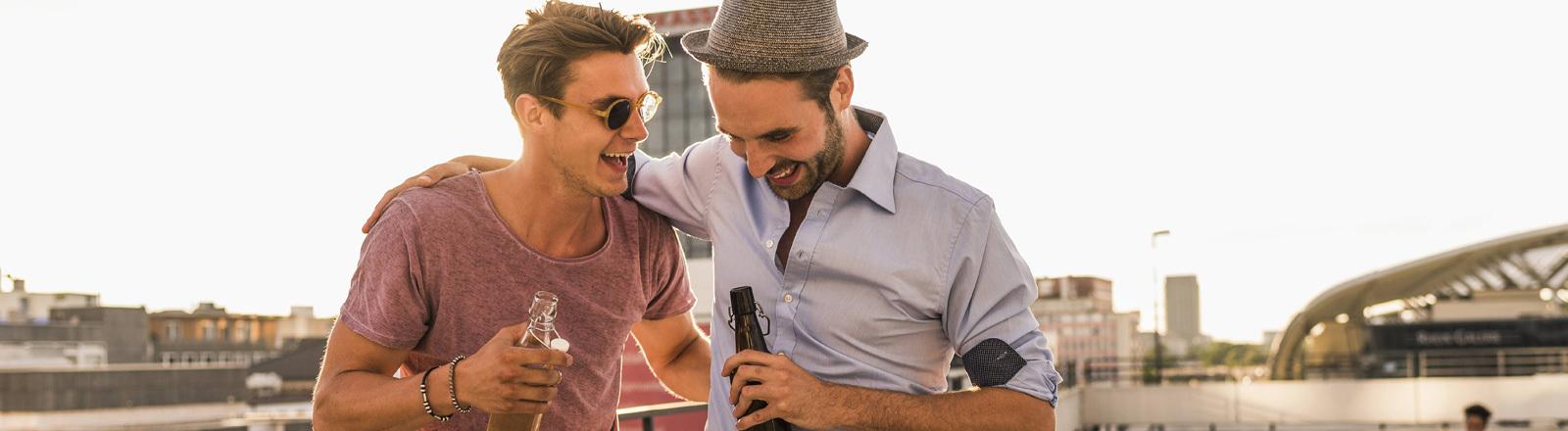 Zwei Männer auf dem Dach eines Parkdecks mit Bier in der Hand umarmen sich und reden miteinander.