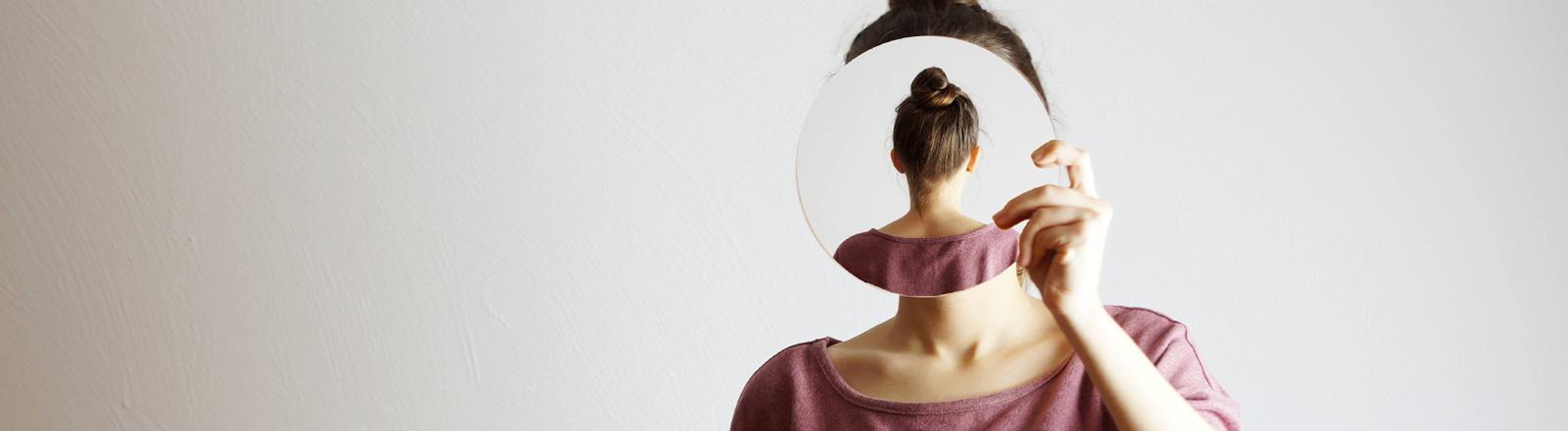 Eine Frau blickt in den Spiegel. Symbolbild für Identitätsfragen.