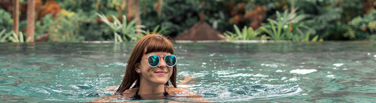 Eine junge Frau schwimmt im Meer - sie trägt eine Sonnenbrille. im Hintergrund sind Palmen.