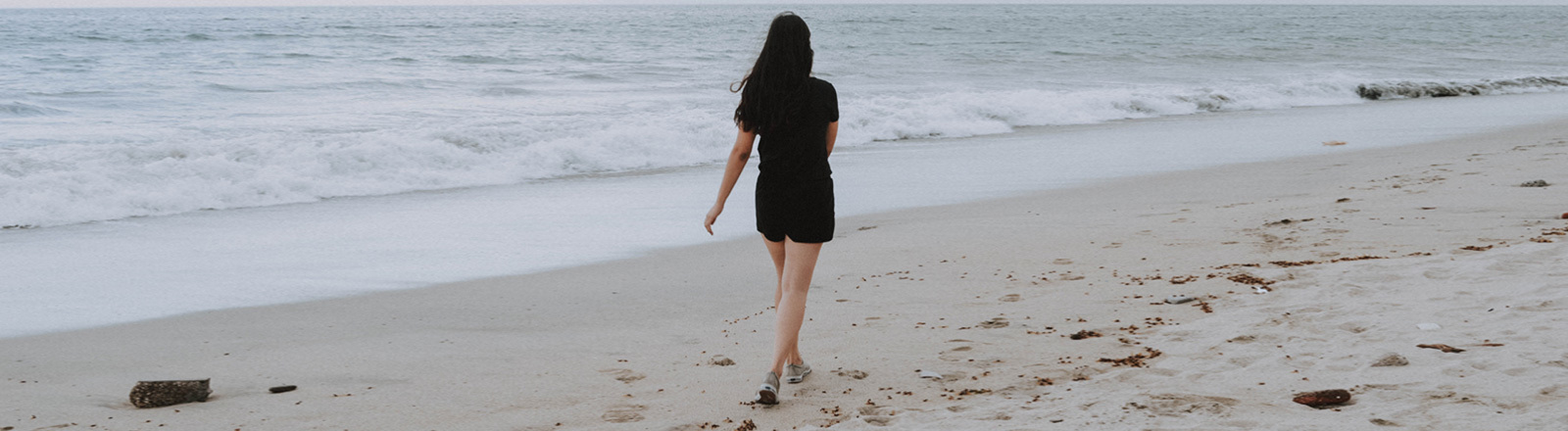 Eine Frau geht selbstbewusst am Strand entlang.