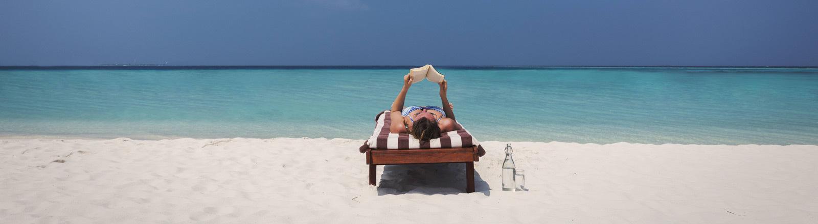 Eine Frau liegt am Strand auf einer Liege und liest ein Buch.