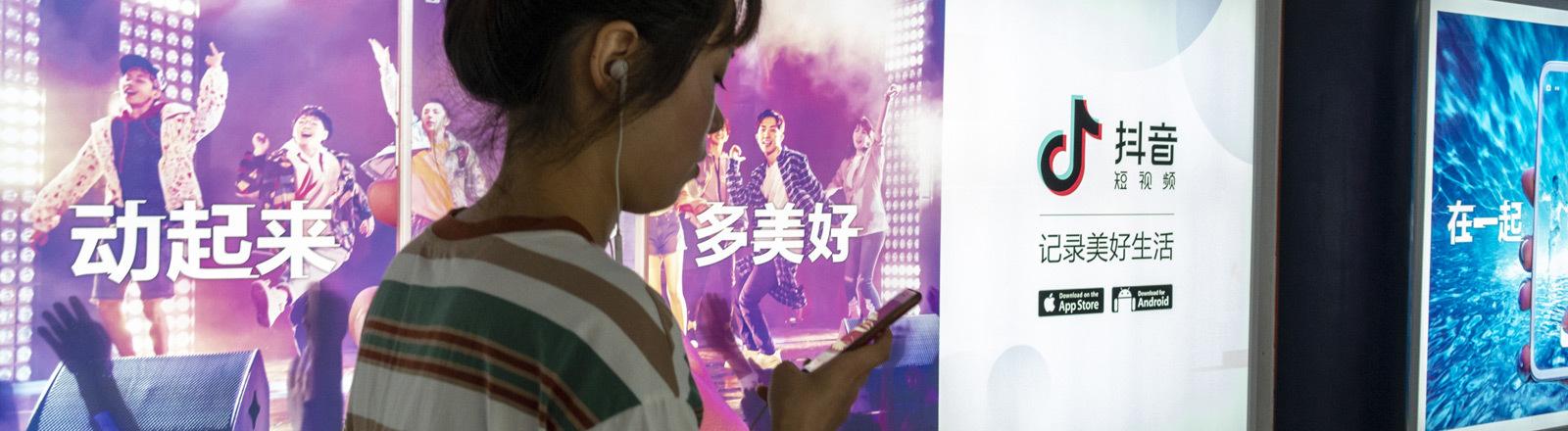 Eine Chinesin in einer Unterführung blickt auf ihr Smartphone.