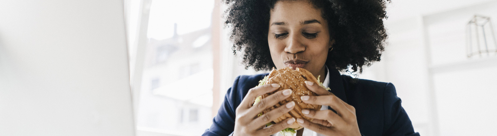 Eine Frau isst einen Burger.