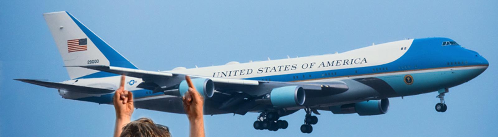 Ein Mann streckt die Mittelfinger Richtung Air Force One aus.