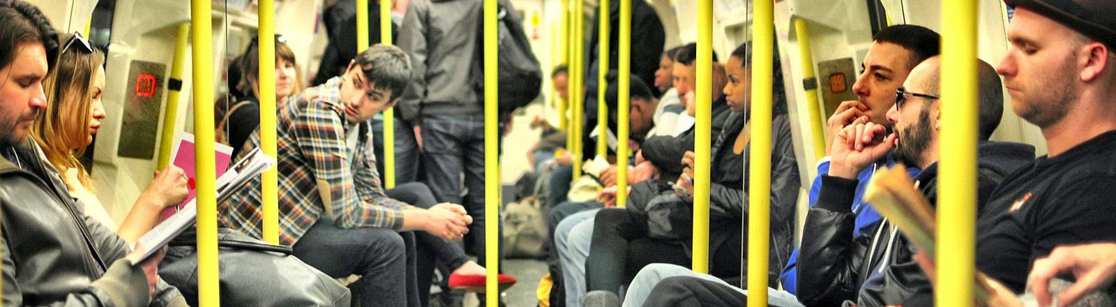 Menschen sitzen dicht an dicht in einer Bahn.