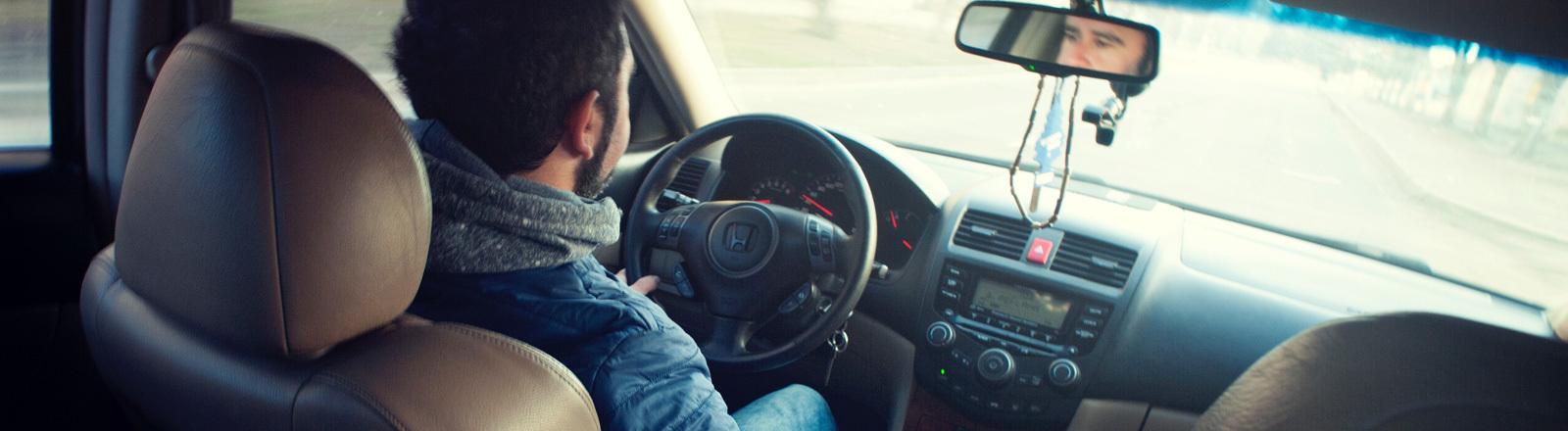 Ein Mann sitzt entspannt im Auto und fährt auf der Straße.
