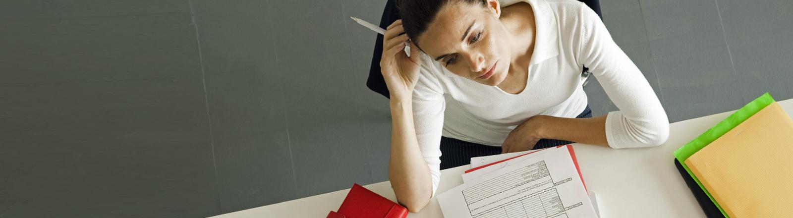 Eine Frau am Schreibtisch denkt nach.