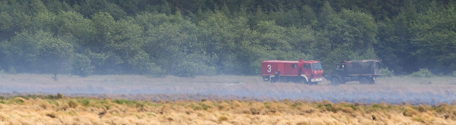 Ein Feuerwehrfahrzeug steht am Donnerstag (15.07.2010) in Meppen (Landkreis Emsland) hinter einem verkohlten Gelände der Wehrtechnischen Dienststelle.