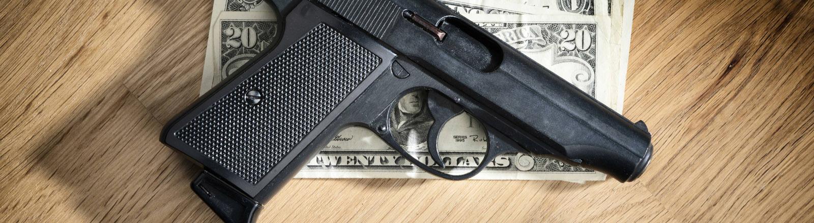 Pistole und Dollarscheine.