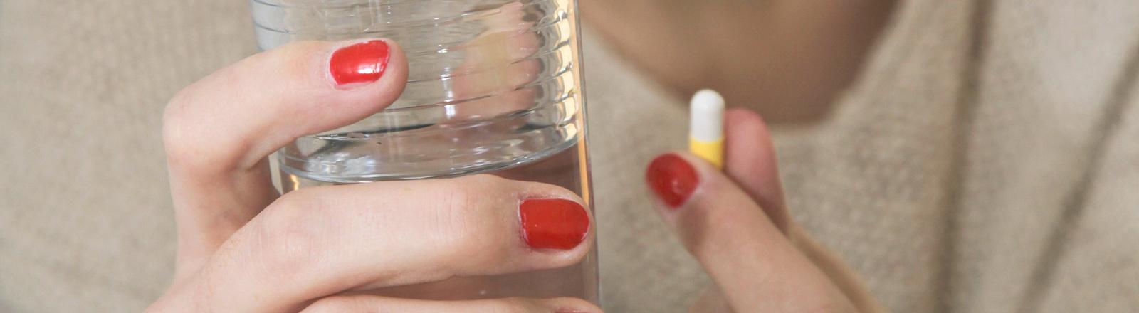 Eine Frau nimmt eine Pille - in der anderen Hand hält sie ein Wasserglas.