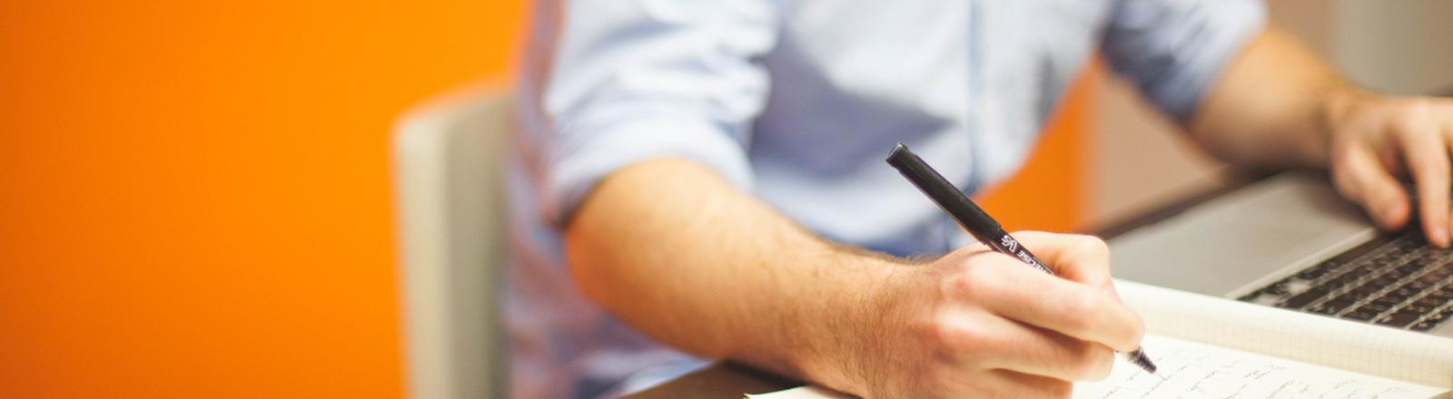 Ein Mann, der nicht ganz erkennbar ist, sitzt vor einem Laptop und schreibt parallel in ein Notizbuch.