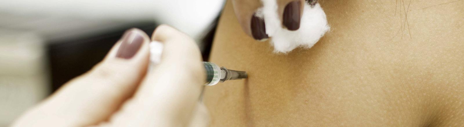 Grippeimpfung - eine Ärztin sticht einer Patientin mit der Nadel in den Arm.