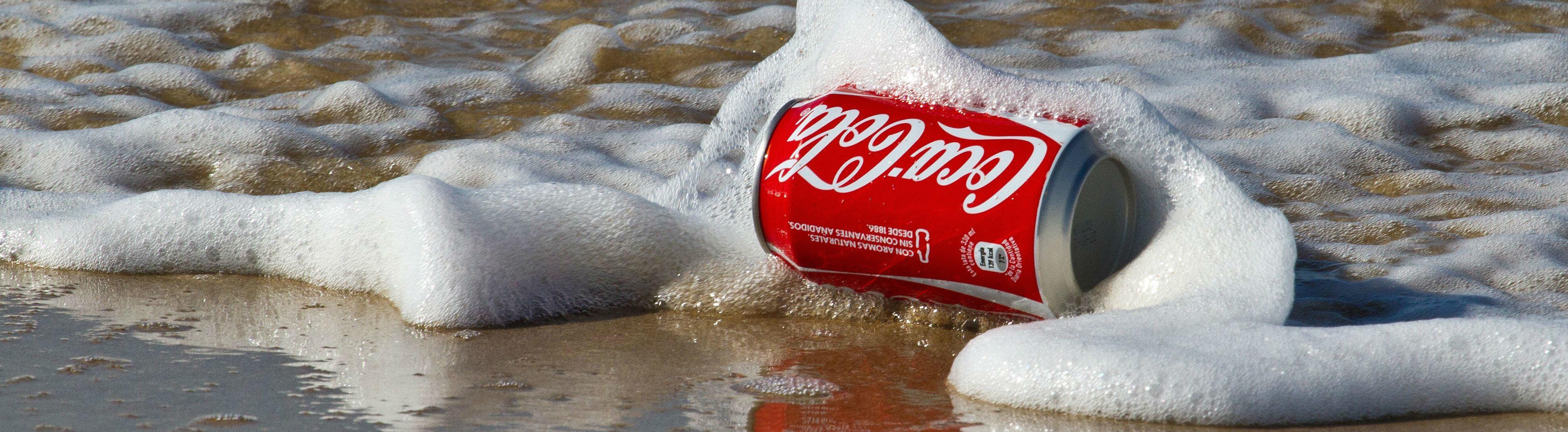 Eine Coladose im Meer.