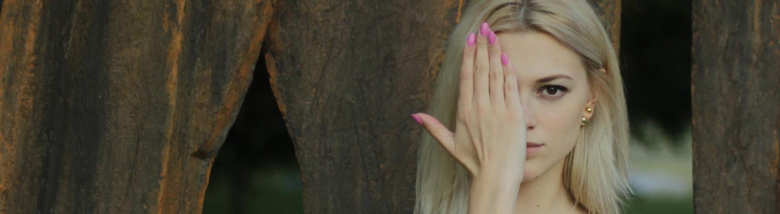 Eine Frau hält sich die Hand vor das halbe Gesicht.