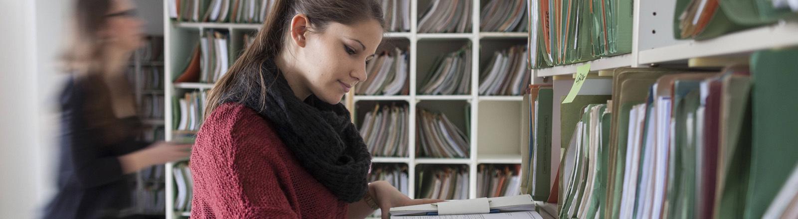 Eine Mitarbeiterin steht im Finanzamt Bonn und liest in Papierakten.