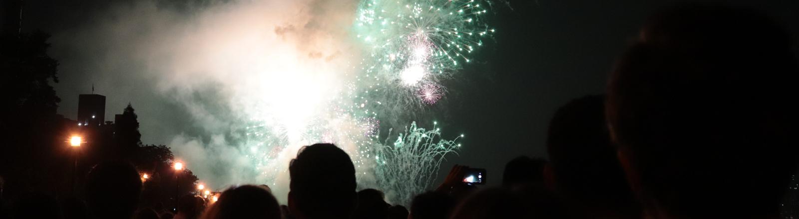 Menschen vor Feuerwerk und Rauch