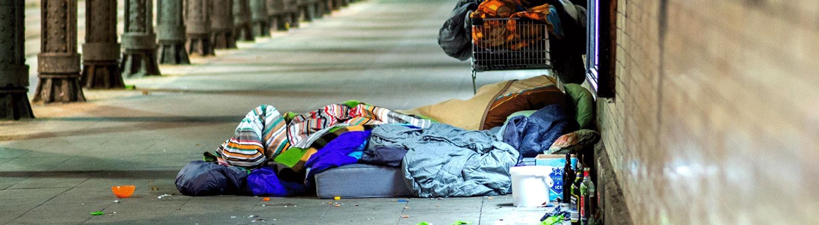 Wohnungslose Frau schläft unter einer Brücke.