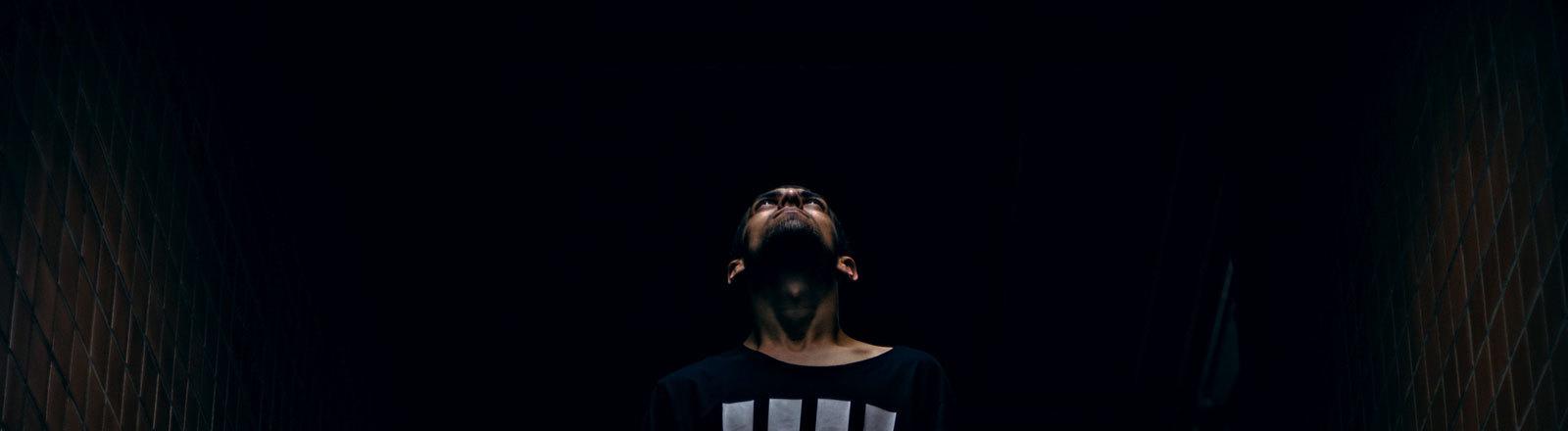 Mann blickt im Dunkeln nach oben.