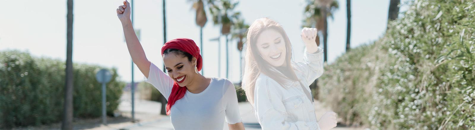 Symbolbild Ghosting: Zwei junge Frauen tanzen auf einer Straße - eine Frau wirkt durchsichtig - wie ein Geist.