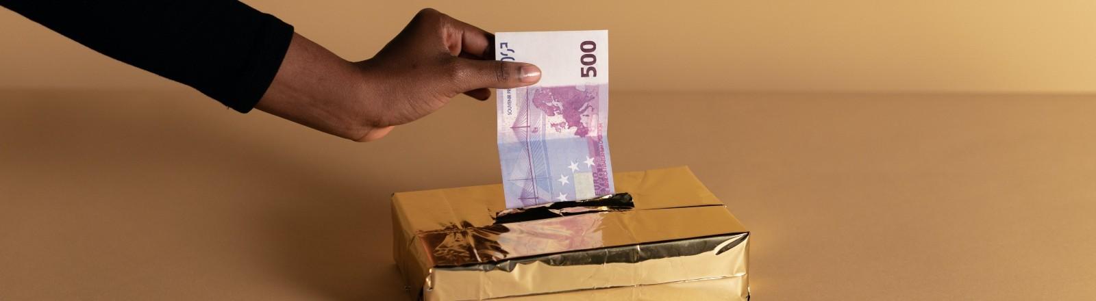 Aus einer Box für Taschentücher zieht eine Hand einen 500-Euro-Schein raus.