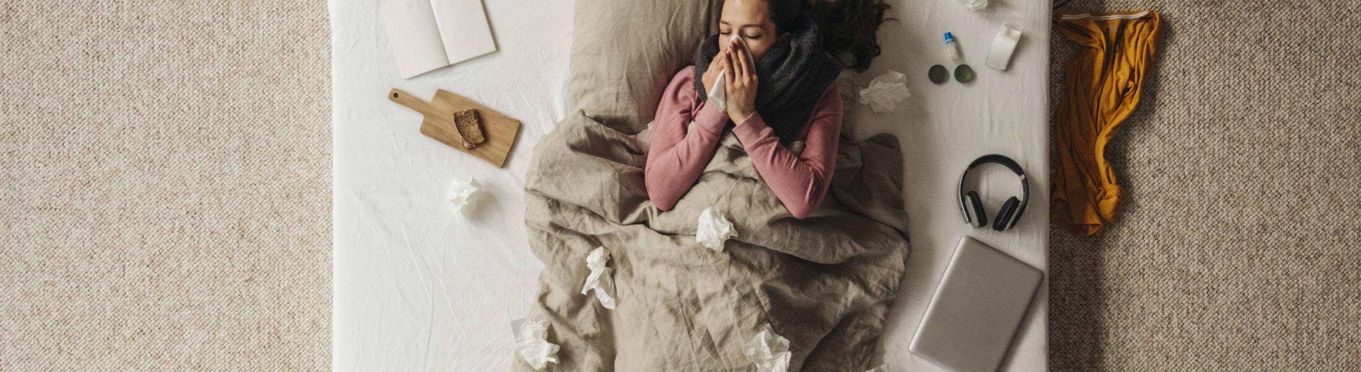 Eine Frau liegt im Bett und um sie herum liegen viele benutzte Taschentücher.