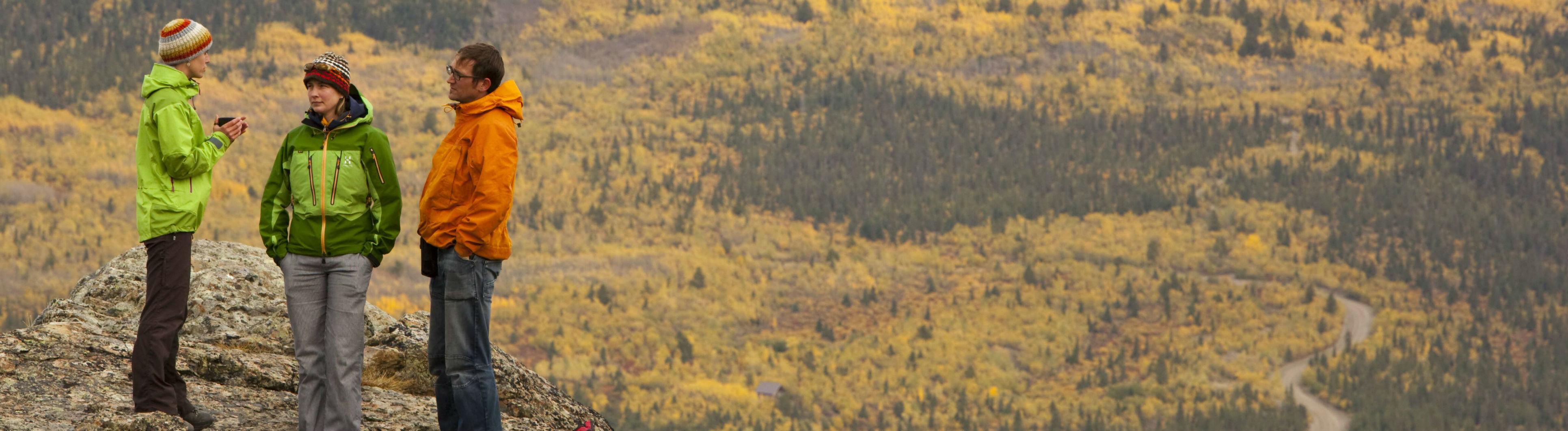 Drei Menschen in Funktionskleidung stehen in einer Berglandschaft und unterhalten sich.