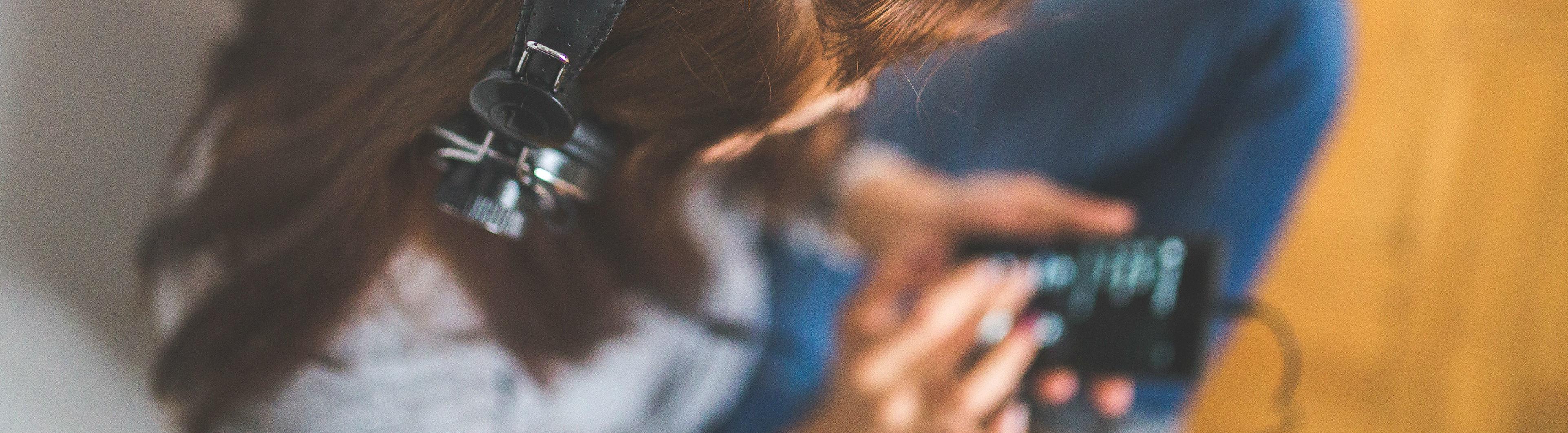 Eine Frau mit Kopfhörern hält ein Smartphone in der Hand und streamt Musik.