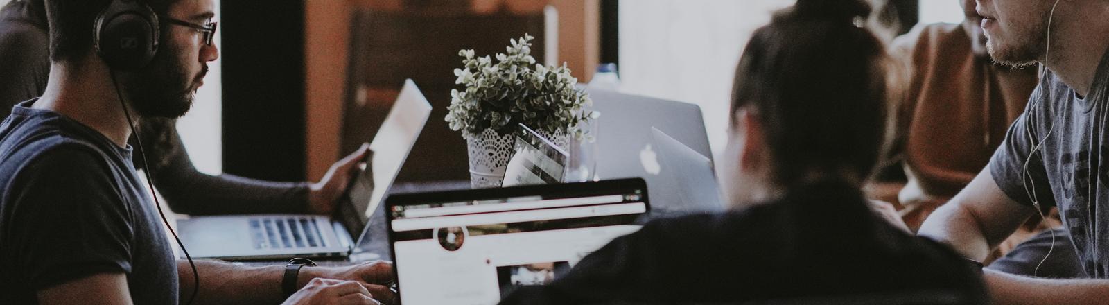 Menschen am Tisch vor ihren Laptops