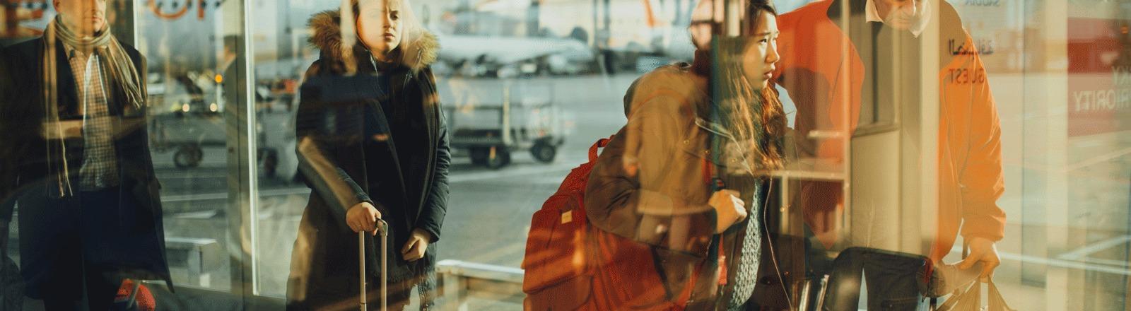 Menschen vor Abflug am Flughafen hinter einer Glasscheibe.