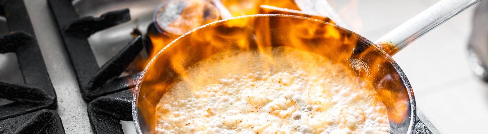 Ein Koch bereitet etwas in einer Pfanne vor, beim Kochen entstehen Flammen.