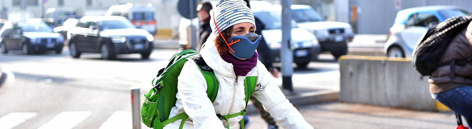 Eine Fahrradfahrerin trägt eine Atemmaske, um sich vor der Luftverschmutzung zu schützen.