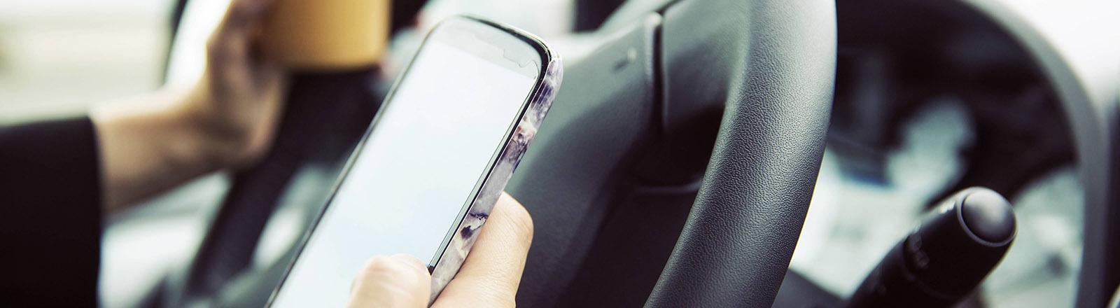 Eine Frau hält ihr Smartphone und einen Kaffeebecher hinter dem Lenkrad in der Hand.