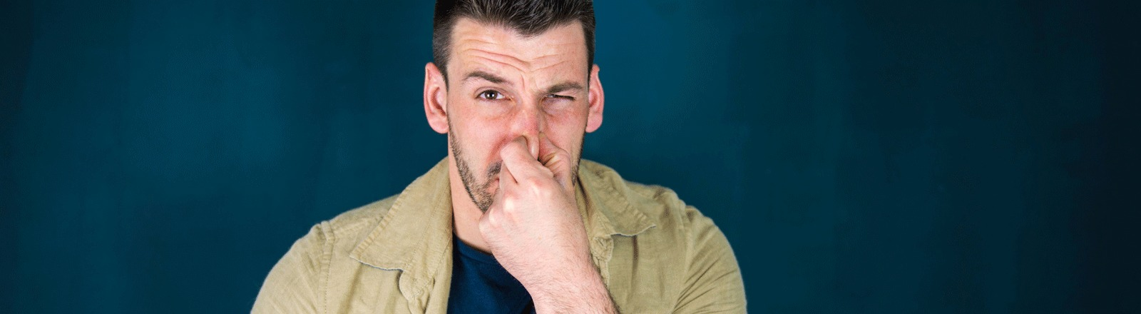 Ein Mann hält sich die Nase zu, weil es stinkt.
