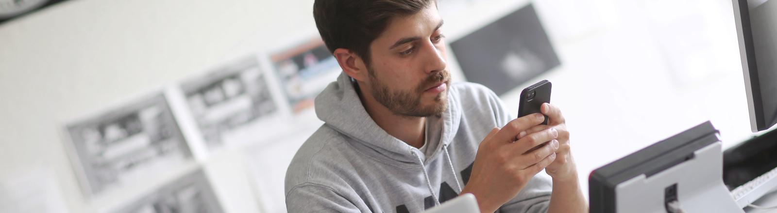 Daniel Bröckerhoff sitzt am Schreibtisch und schaut auf sein Handy.