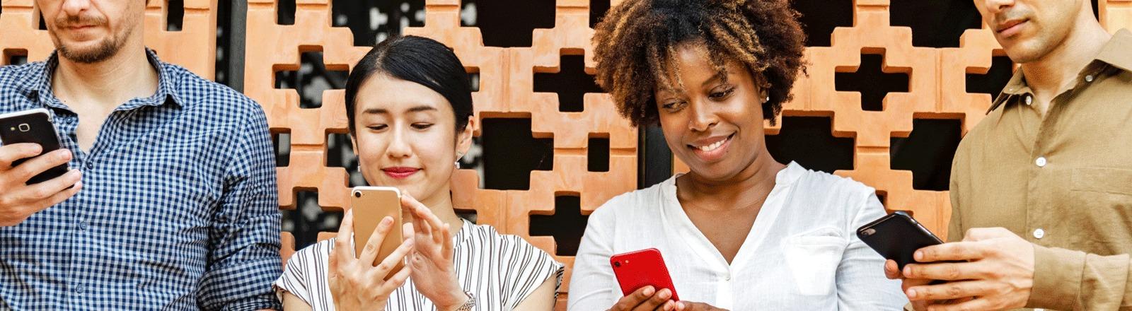 Vier Menschen, zwei Männer (außen) und zwei Frauen (in der Mitte) stehen nebeneinander - alle schauen auf ihr Smartphone.