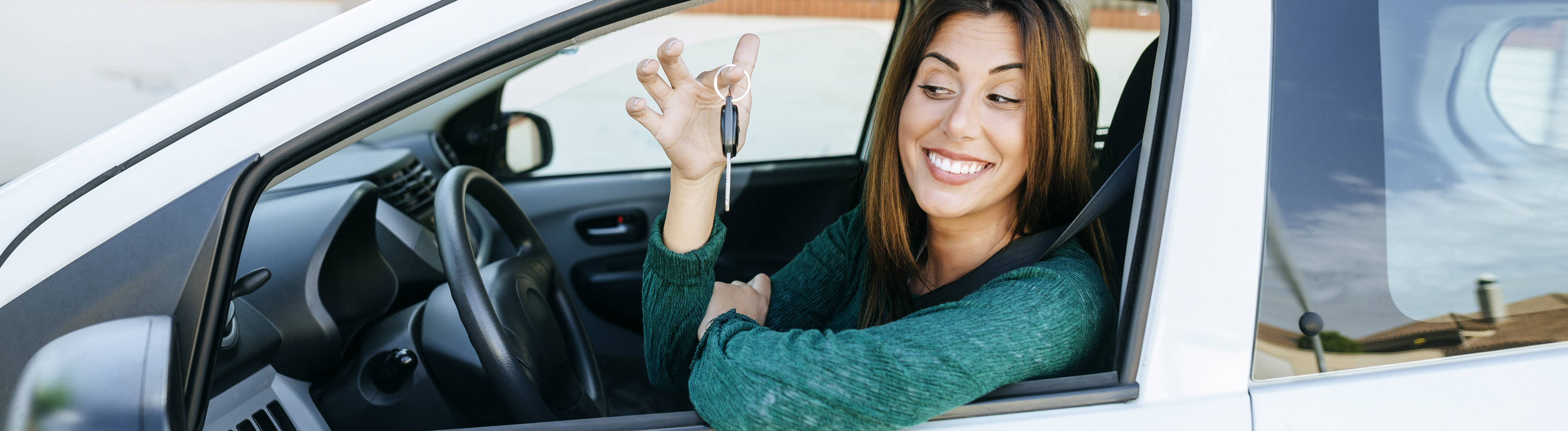 Frau in Auto mit Schlüssel