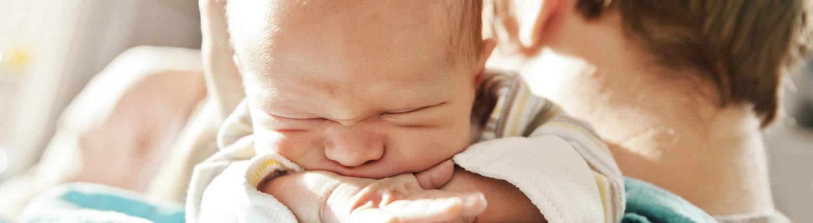 Ein Vater hält kurz nach der Geburt seinen Sohn auf dem Arm.