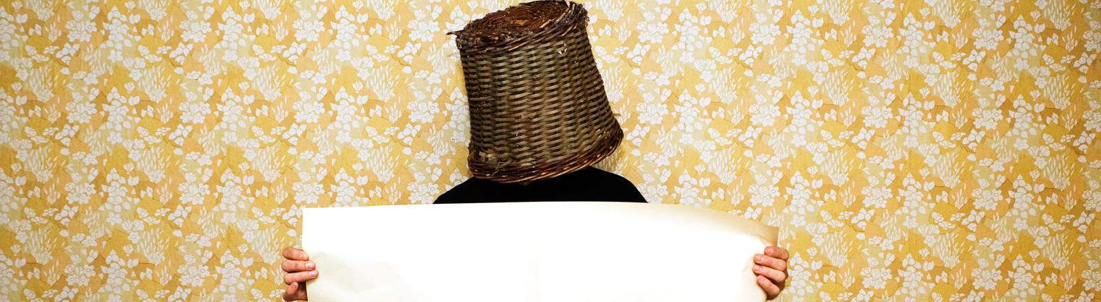 Mann mit Eimer auf dem Kopf vor einer Mustertapete.