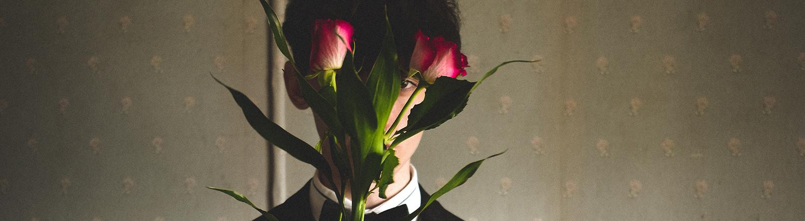 Mann versteckt sich hinter Rosenstrauß.
