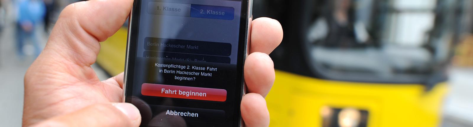 Ein Fahrgast bucht über eine Ticket-App eine Fahrkarte.