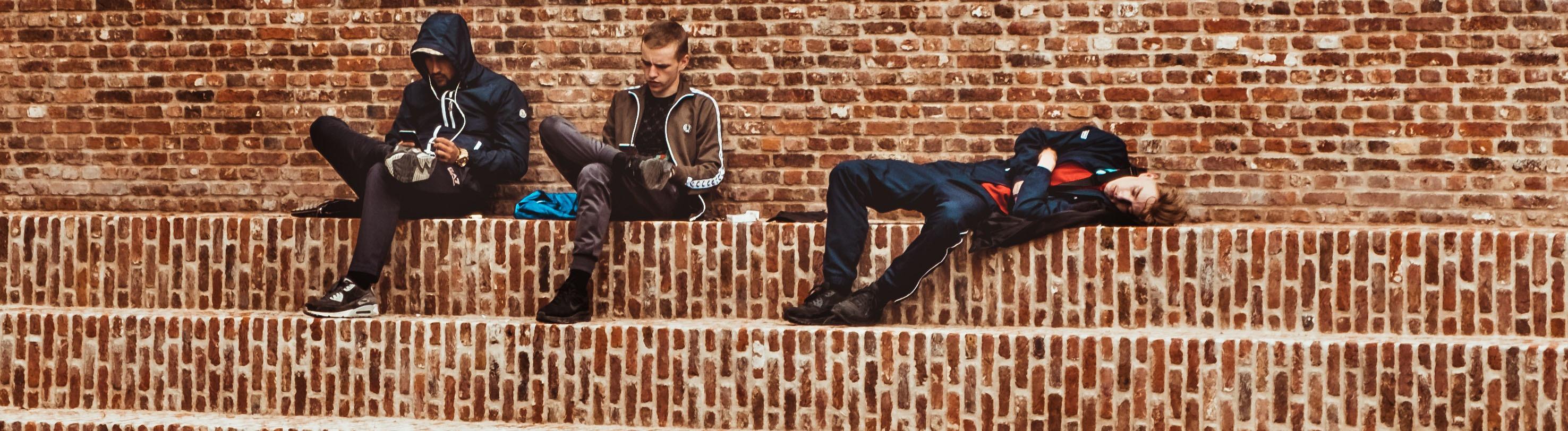 Drei Männer sitzen auf Stufen und schauen in ihr Smartphone.