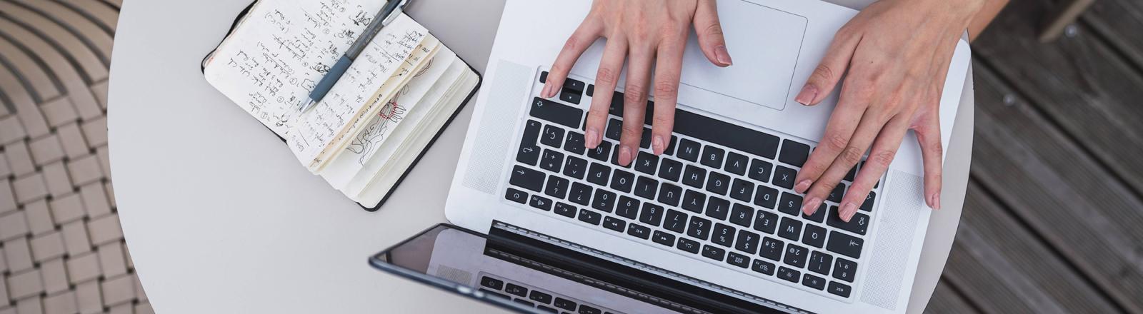 Eine Frau schreibt an einem Laptop.