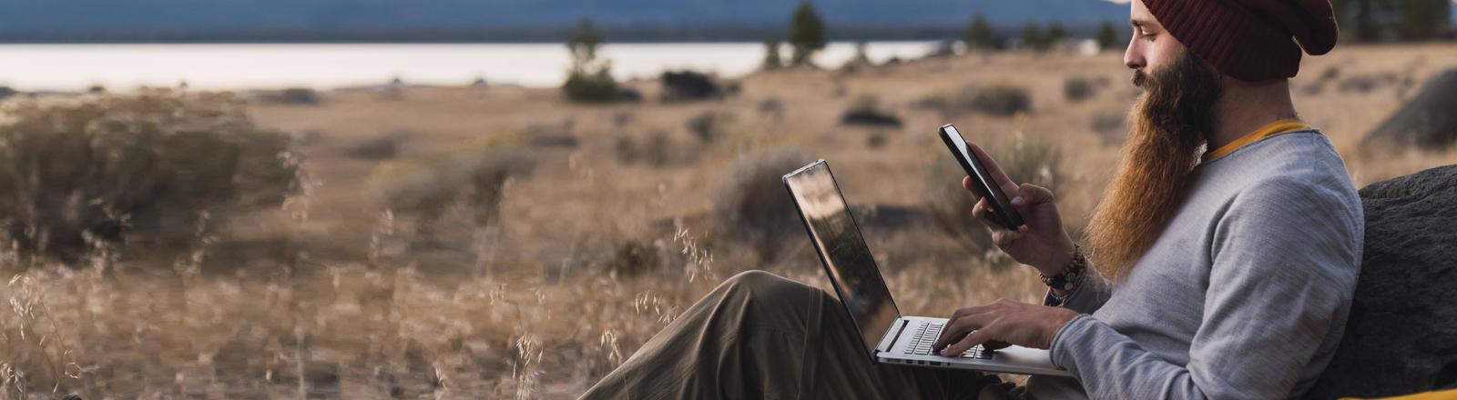 Ein bärtiger Mann schaut im Urlaub auf Handy und Laptop.